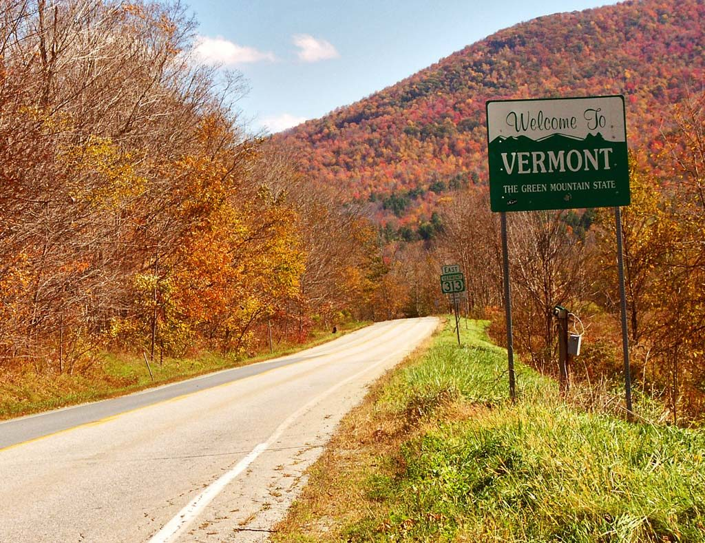 "A beautiful view with a road, colorful  autumn trees and a road sign ""Welcome to Vermont"" on the right where you can find the finest maple syrup"