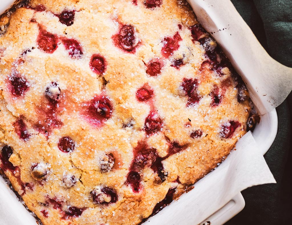 A whole, beautiful Cranberry Maple Saucy Cake in a white baking pan.