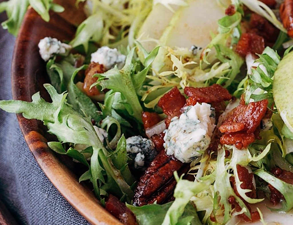 Bowl of Asian Salad with pecans, topped with blue cheese.