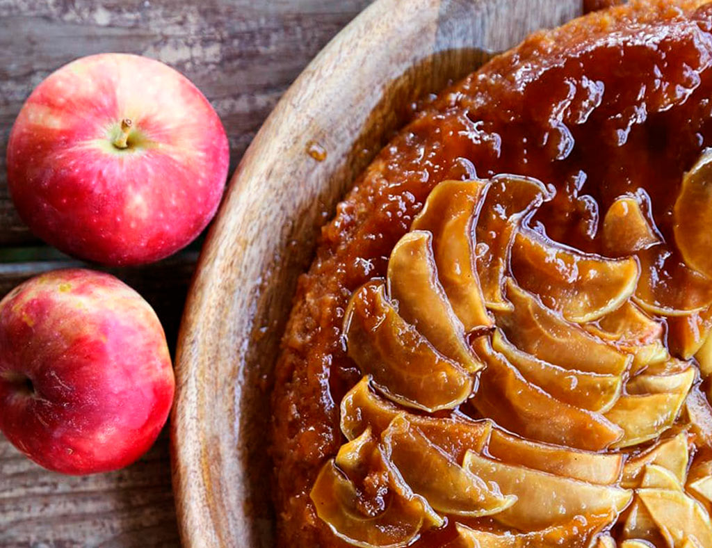 Maple Upside-Down Cake with two red apples on the table on the left