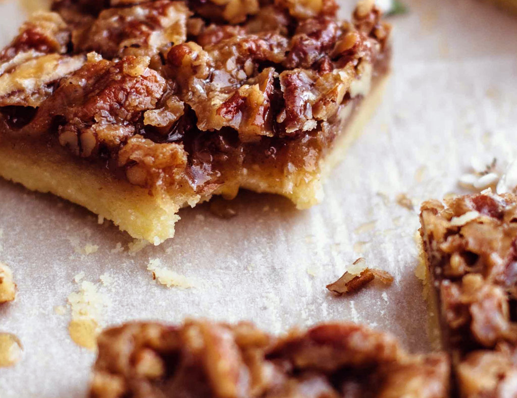 A nutty maple bar topped with pecans without a piece that was bitten off.