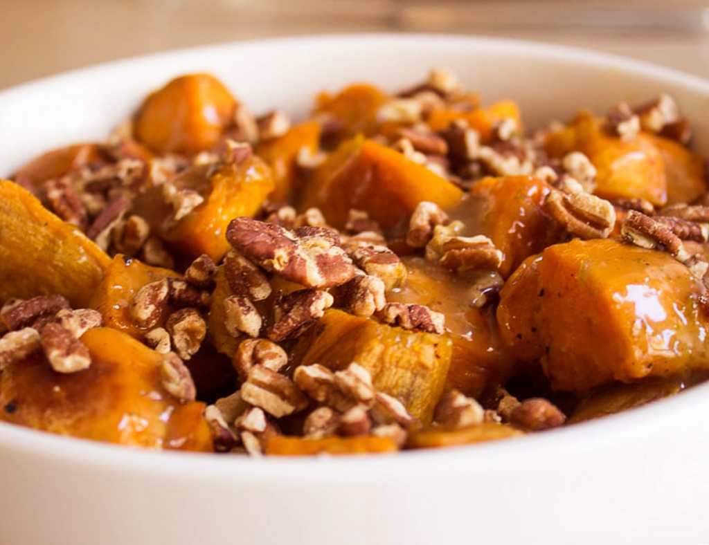 A white bowl with Maple Sweet Potatoes and Pecans.