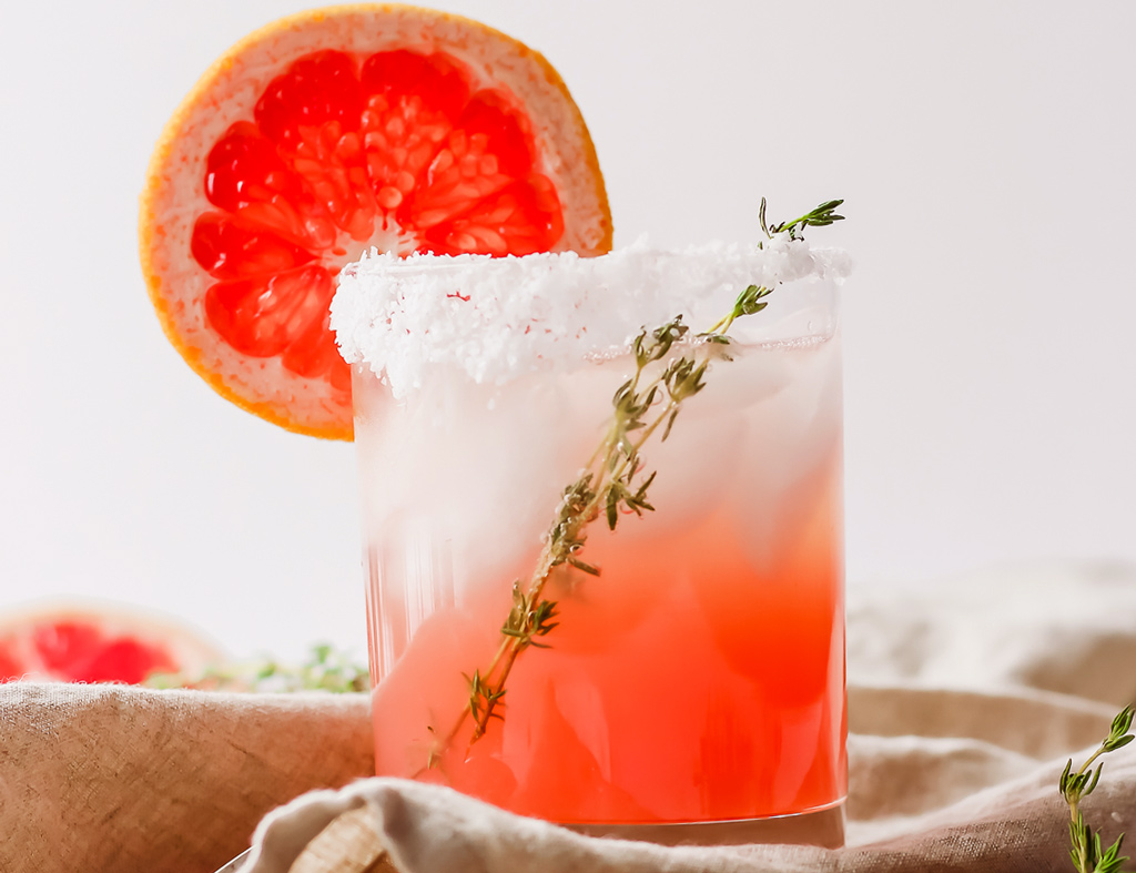 Beautiful glass with The Paloma Cocktail garnished with a slice of grapefruit.