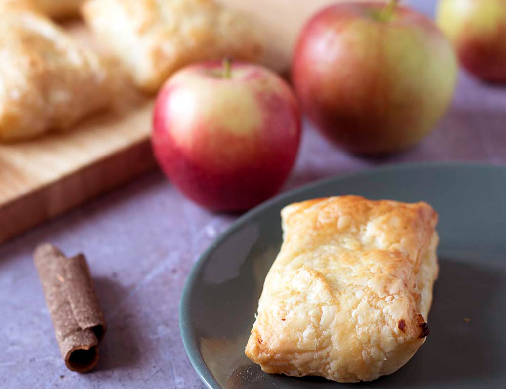 A plate with one Maple Turnover on it and several apples beside.