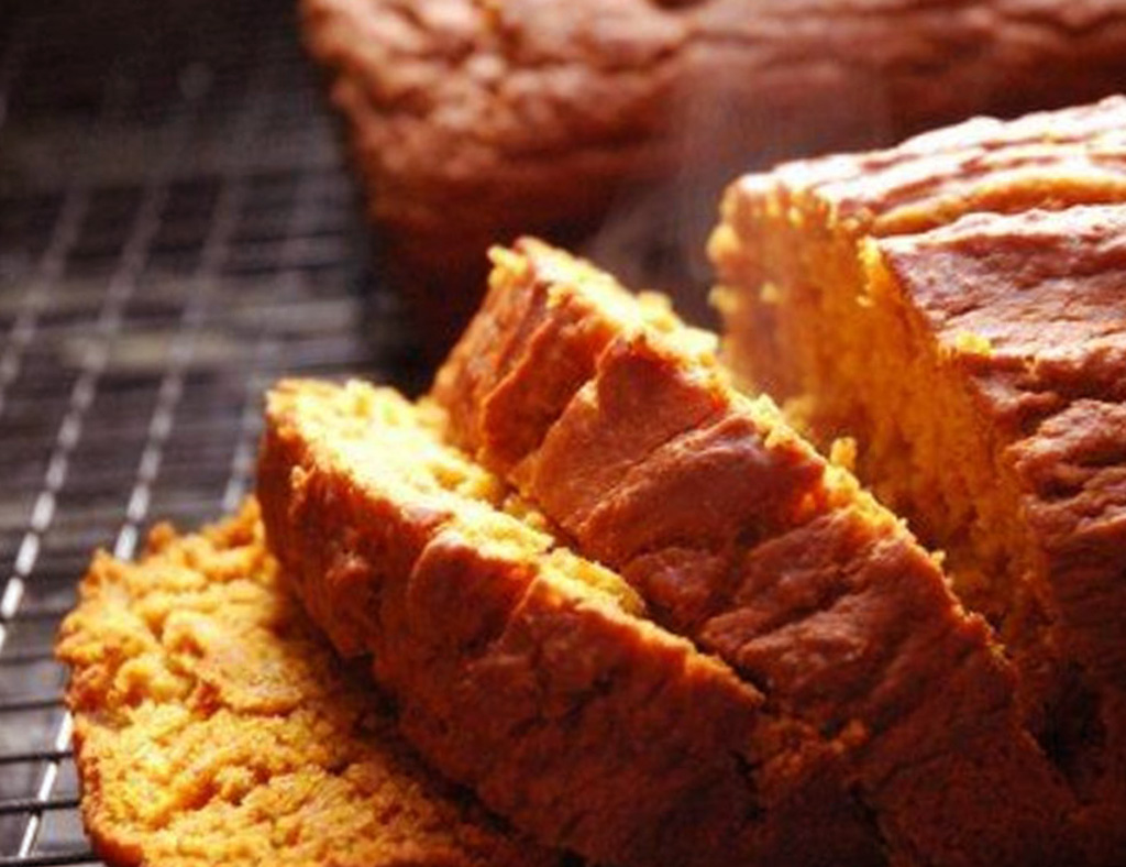 Hot sliced Pumpkin Loaf on a wire rank.
