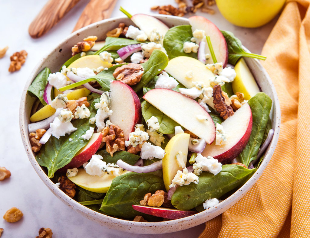 Beautiful bowl with Green Salad With Maple-Cider Vinaigrette in it.